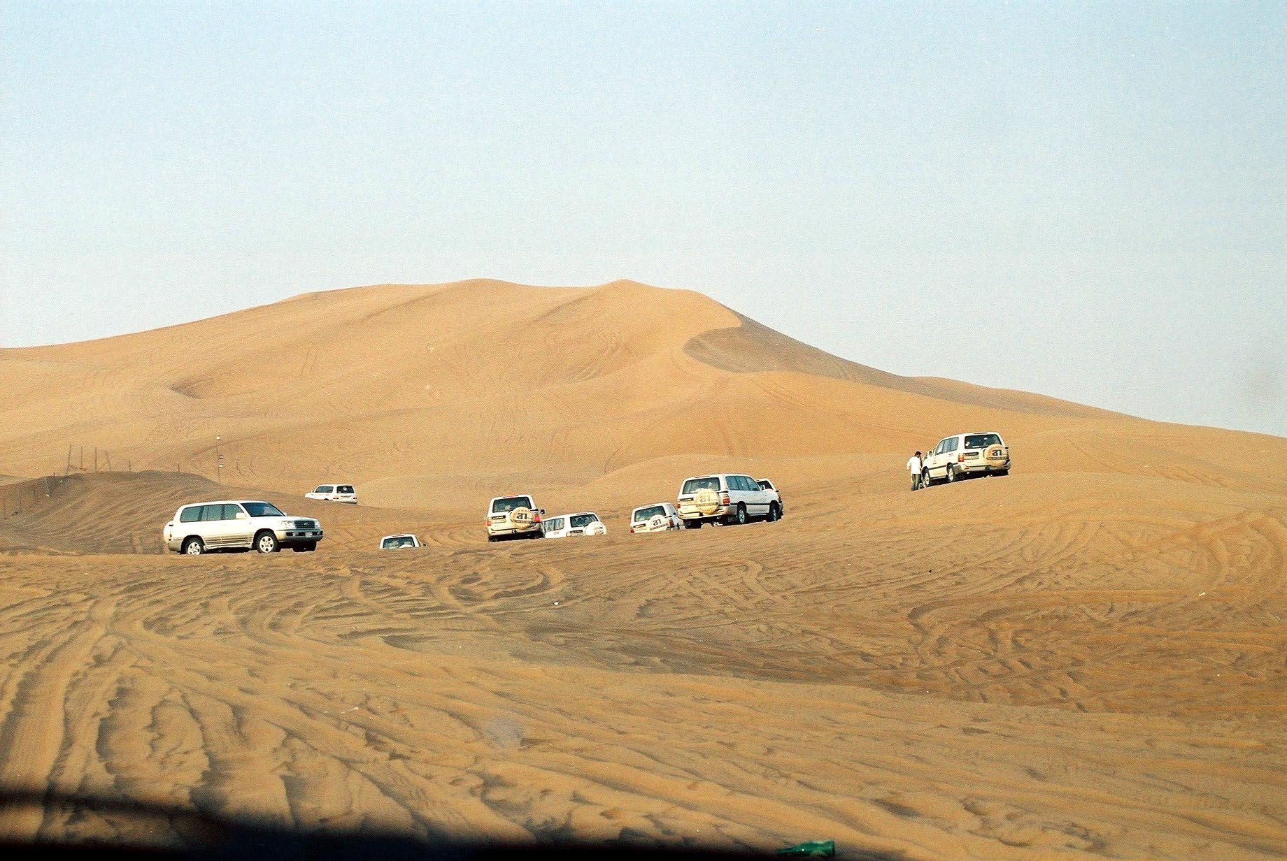 Convoys of land cruisers approaching a big dune